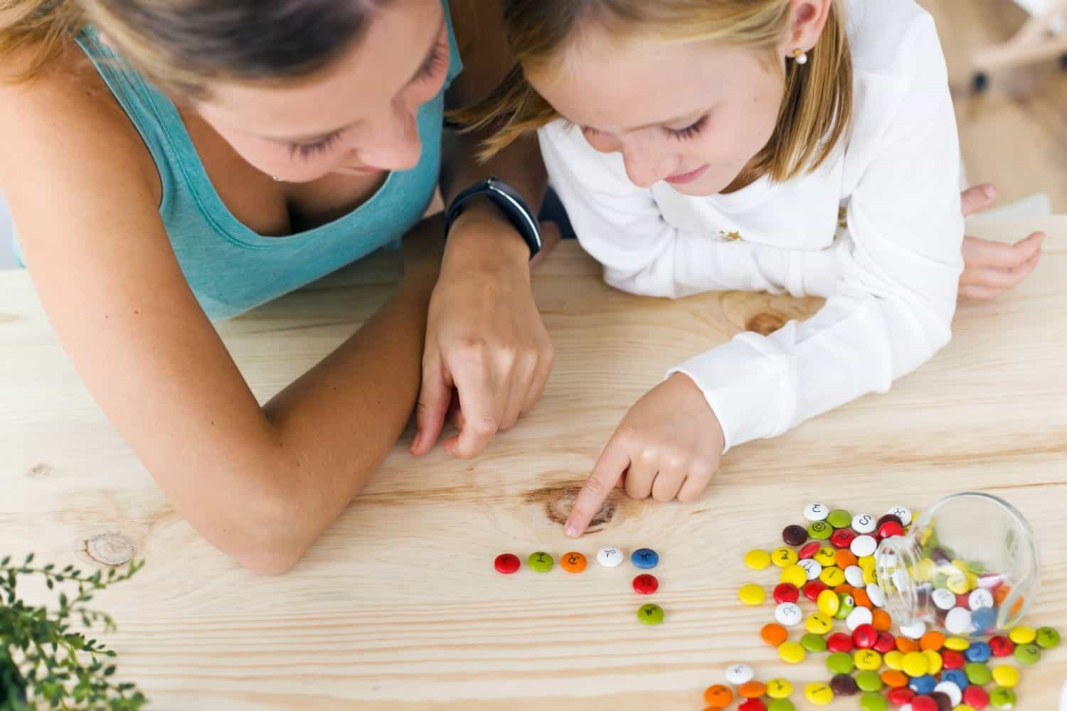 Mother and daughter learning together with counting beans