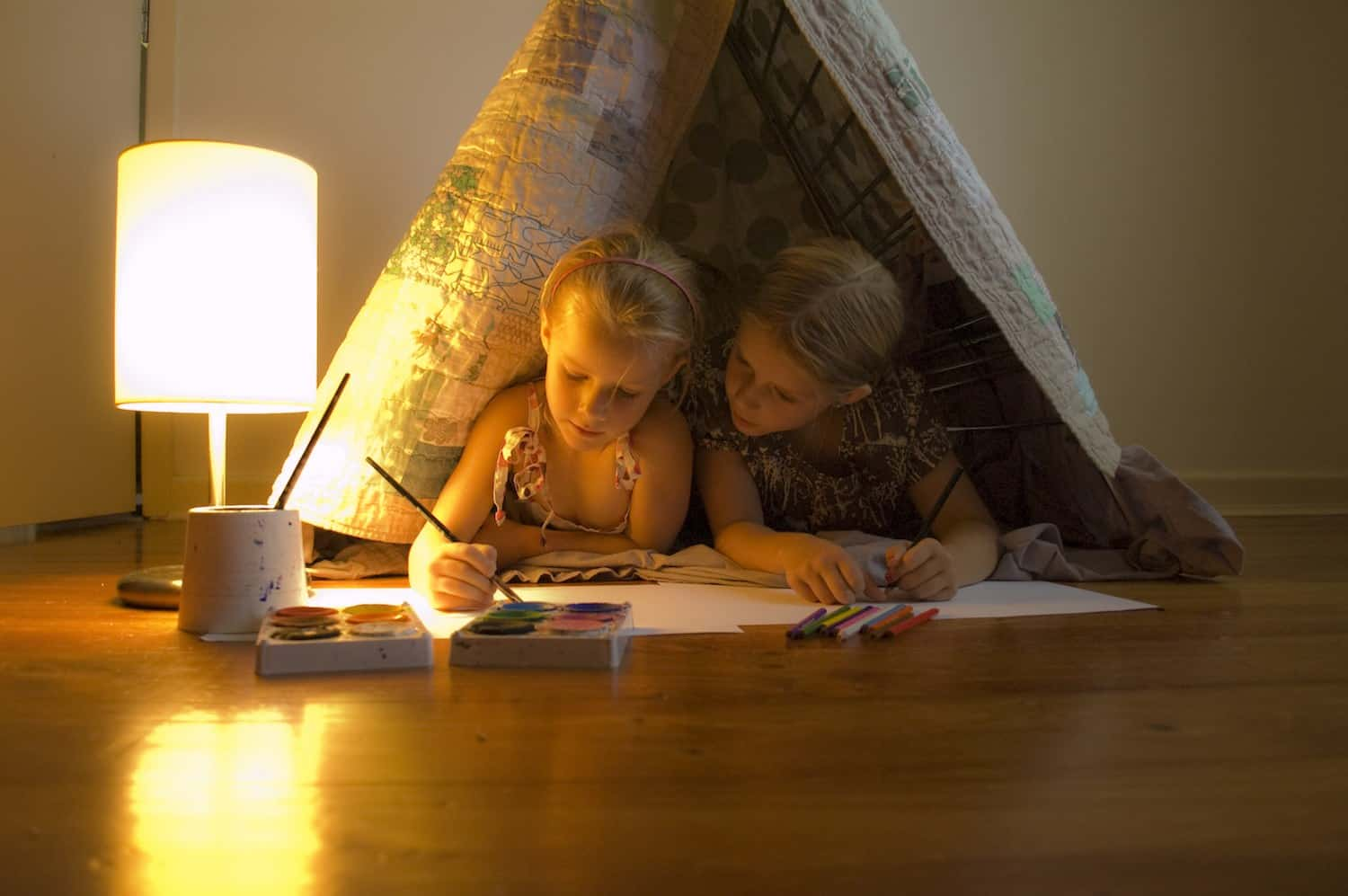 Two girls lay in a teepee doing art work