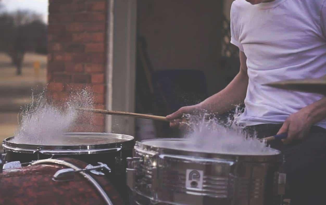 Drummer hits drums splashing water