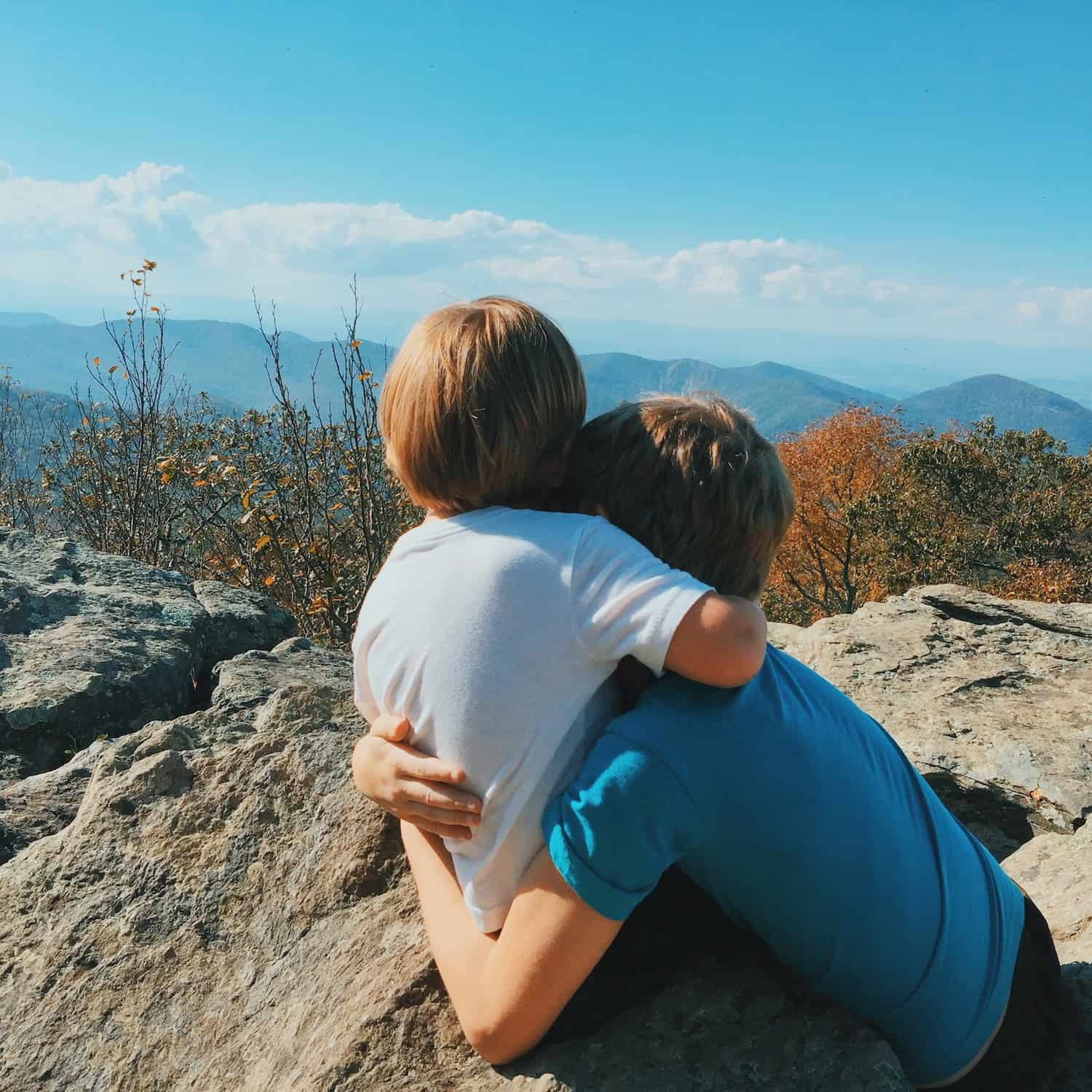 Two kids hug while looking at nature