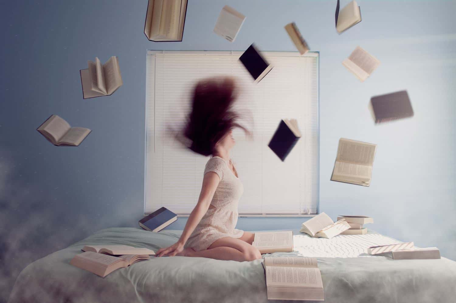 Lady throwing hair back with books flying through the air.