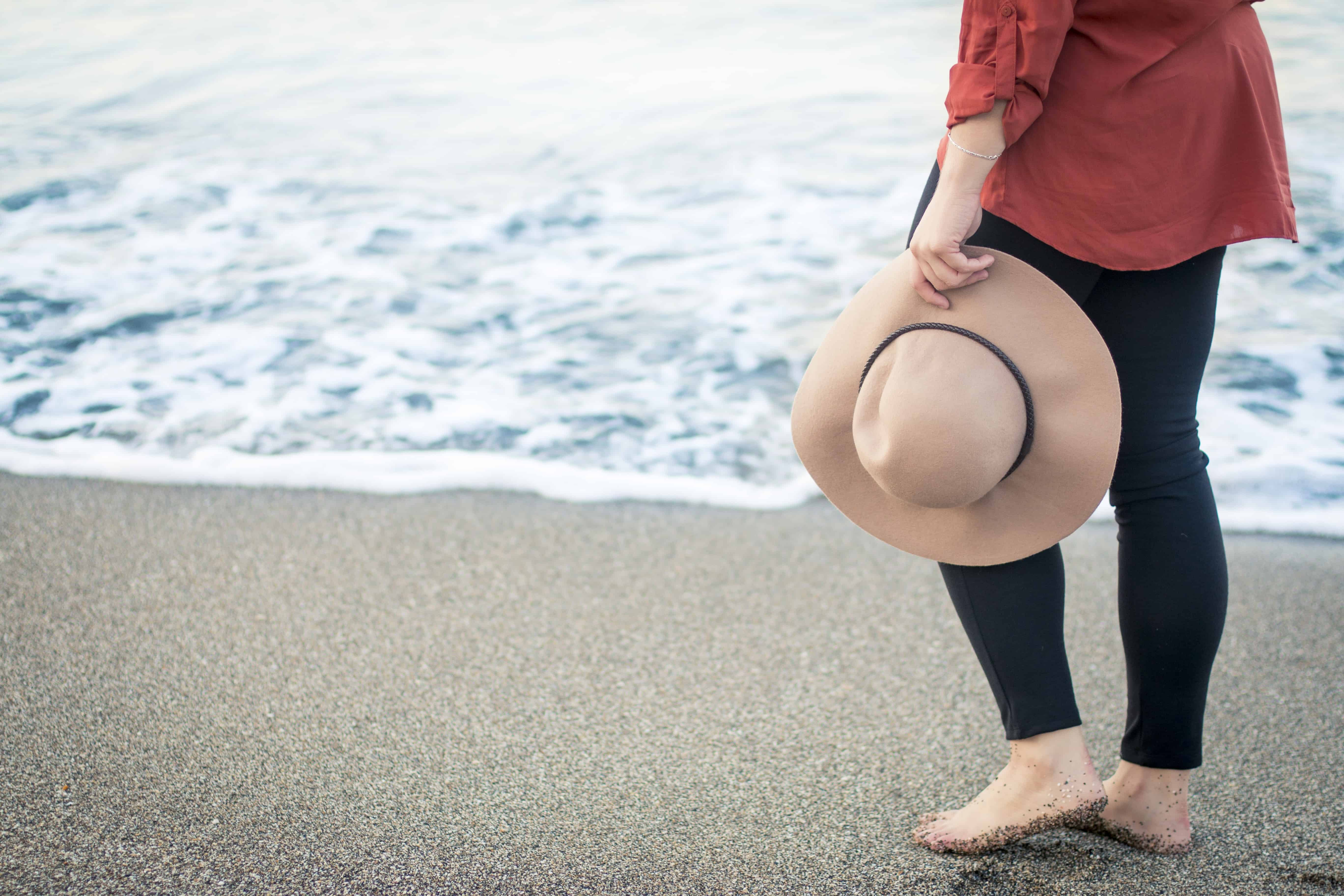Lady holding hat at the beach