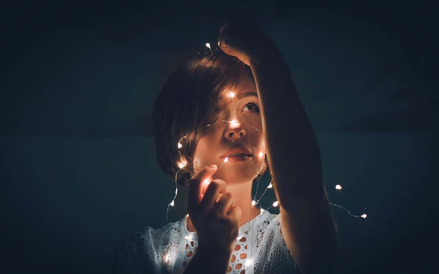 Woman looking at fairy lights confused look on face