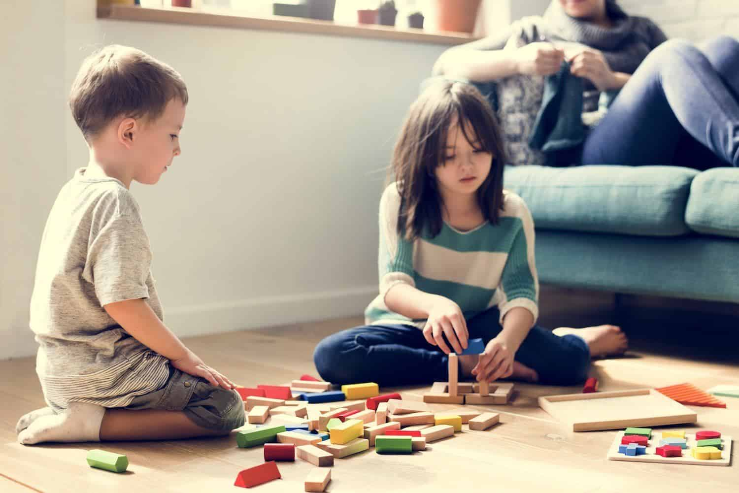 Teaching math to kids: Children playing with blocks on the floor
