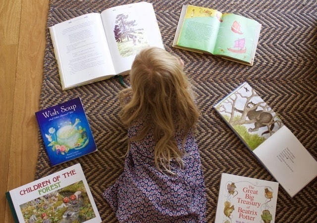 Girl looking at books spread on floor