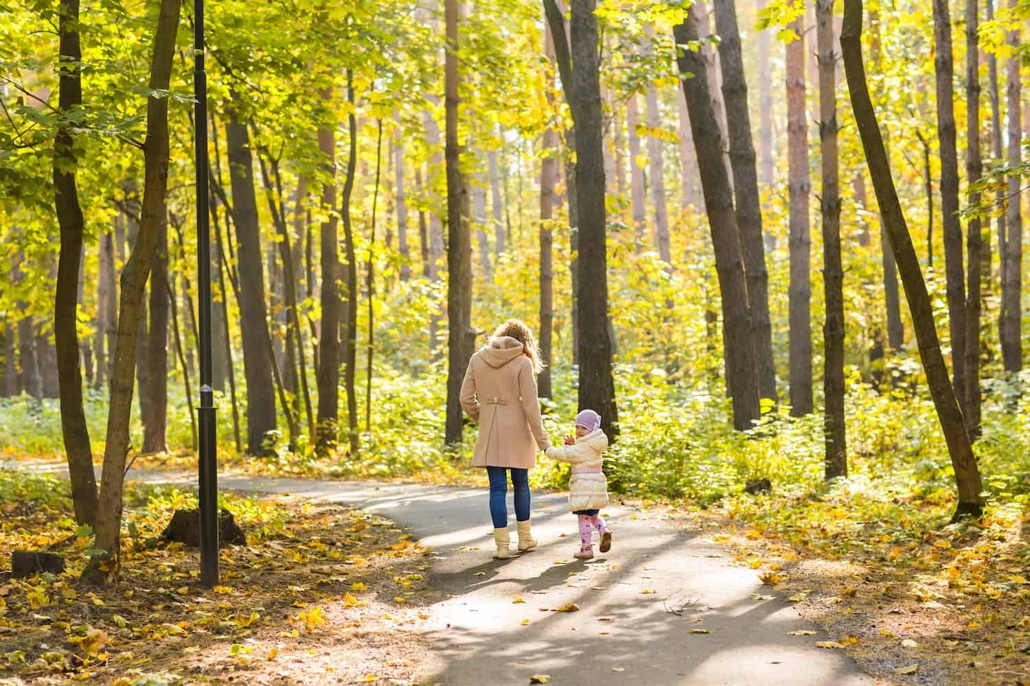 Mother and child walking in autumn park
