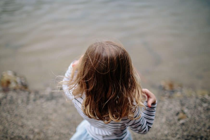 Young girl looking into a lake