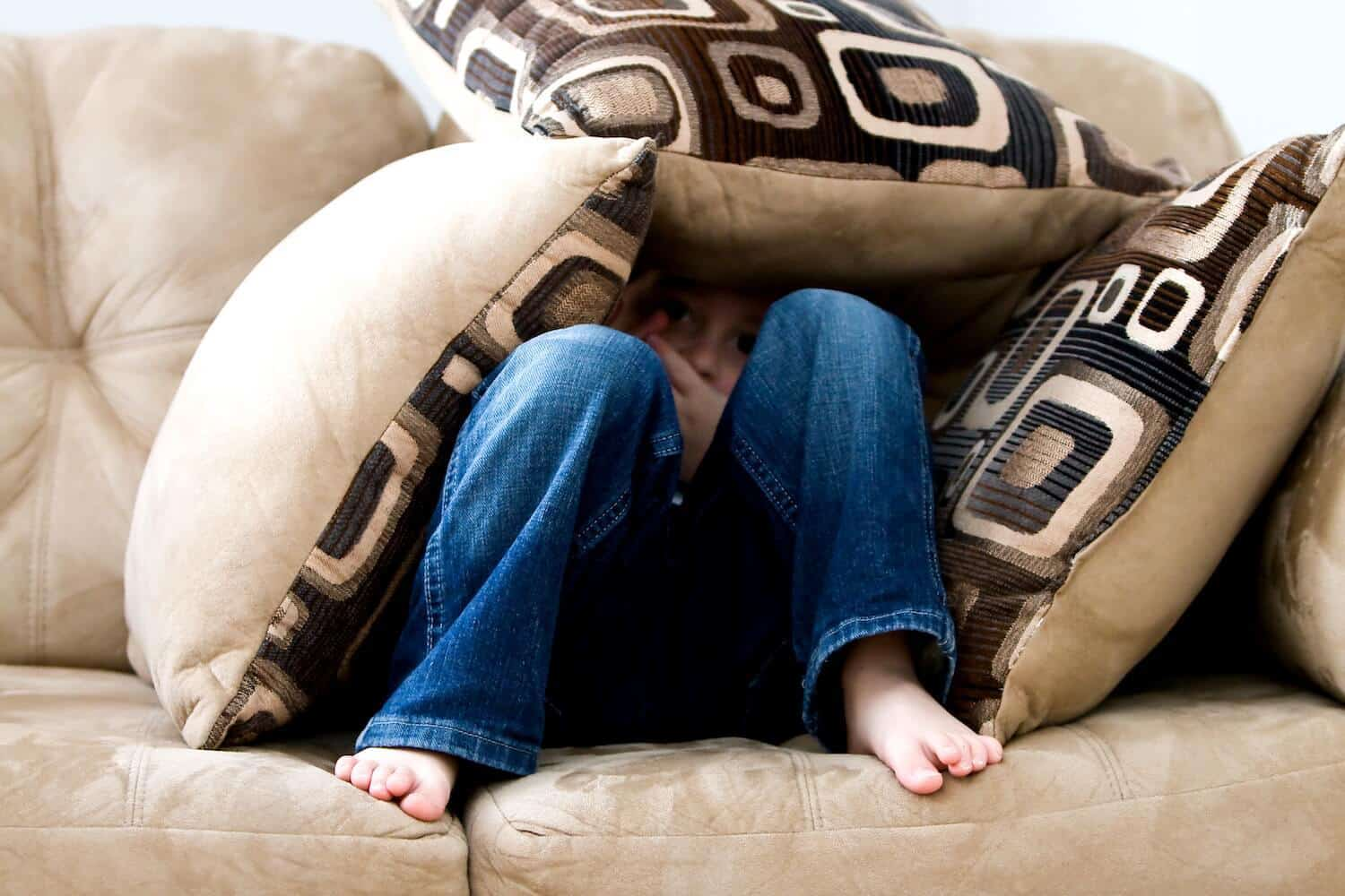 child hiding on couch in pillows